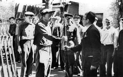 Работник райкома вручает оружие бойцам народного ополчения. Лето 1941 г.
